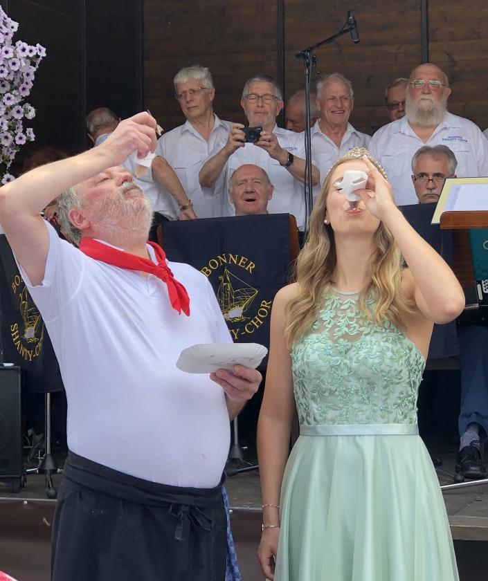 2018: Veranstalter Werner Pommer und die Brunnenkönigin vollziehen den traditionellen Matjesbiss (Foto: Imke Weiler)